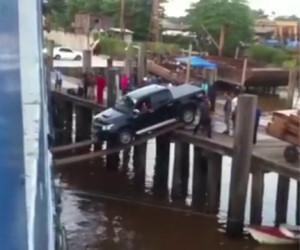 Caricano un'automobile sulla nave usando due pedane di legno