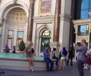 Ragazza si mette in posa sul bordo di una fontana e cade dentro
