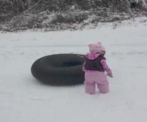 La bambina non sa scivolare sulla neve, qualcuno le mostra come si fa
