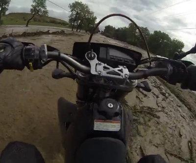 Motociclista attraversa un'inondazione