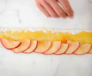 Stende uno strato di pasta sulle mele, il risultato finale è spettacolare