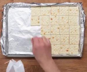 Mette i crakers su una teglia per preparare un dolce davvero strano