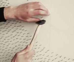 Inserisce migliaia di chiodi su una parete e crea un'opera d'arte
