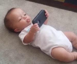 Mentre questo bimbo tiene in mano il telefono fa qualcosa di divertente