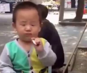 Bimbo di 2 anni fuma per strada