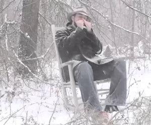 Seduto sulla neve suona un brano con la propria armonica