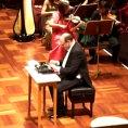 Si esibisce con una macchina da scrivere di fronte l'orchestra