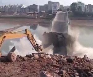 Una gru distrugge un ponte