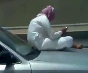 Arabo sul cofano di un'auto invia sms