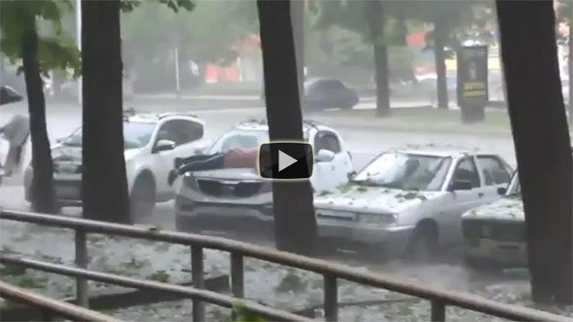 Donna russa protegge l'auto dalla grandine col proprio corpo